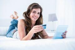 Mujer hermosa que hace compras en línea con su PC de la tableta Imágenes de archivo libres de regalías