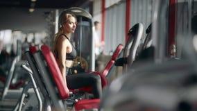 Mujer hermosa que hace ejercicio de la aptitud en el simulador del deporte en club del gimnasio almacen de video