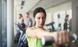 Mujer hermosa que hace ejercicios con pesa de gimnasia en gimnasio La muchacha est? gozando con su proceso de entrenamiento fotos de archivo