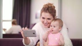 Mujer hermosa que hace el selfie con el bebé Madre con el niño que toma la foto móvil almacen de metraje de vídeo