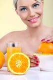 Mujer hermosa que hace el zumo de naranja Fotos de archivo libres de regalías