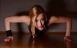 Mujer hermosa que hace flexión de brazos Imagen de archivo libre de regalías