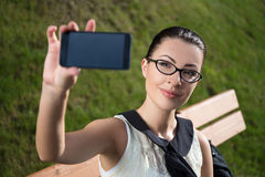 Mujer hermosa que hace la foto del selfie o que muestra algo en smar Imagen de archivo libre de regalías