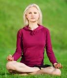 Mujer hermosa que hace la yoga que estira ejercicio Imagen de archivo