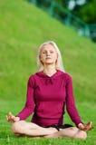 Mujer hermosa que hace la yoga que estira ejercicio Fotografía de archivo libre de regalías
