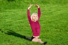 Mujer hermosa que hace la yoga que estira ejercicio Imágenes de archivo libres de regalías