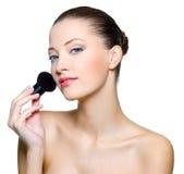 Mujer hermosa que hace maquillaje en cara Fotos de archivo