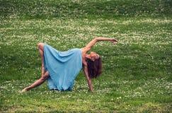 Mujer hermosa que hace yoga en prado fotografía de archivo