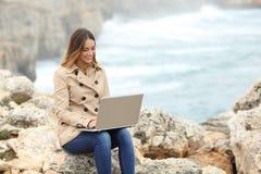 Mujer hermosa que hojea su ordenador portátil en invierno en la costa Imágenes de archivo libres de regalías