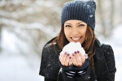 Mujer hermosa que juega con nieve en parque Fotos de archivo