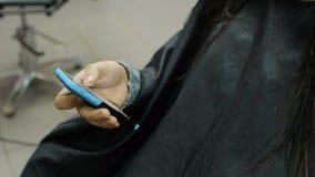 Mujer hermosa que juega con Smartphone en salón de pelo almacen de video