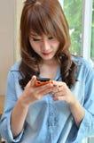 Mujer hermosa que juega con su teléfono móvil Imagenes de archivo