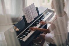 Mujer hermosa que juega el piano Imágenes de archivo libres de regalías