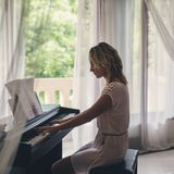 Mujer hermosa que juega el piano Fotografía de archivo