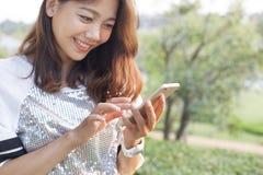 Mujer hermosa que juega y que toca en la pantalla elegante del teléfono en el ou Foto de archivo