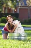 Mujer hermosa que lava su perro de animal doméstico en una tina Fotos de archivo