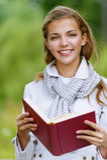 Mujer hermosa que lee el libro rojo Foto de archivo libre de regalías