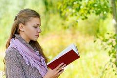 Mujer hermosa que lee el libro rojo Fotografía de archivo