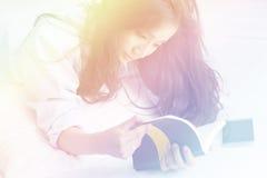 Mujer hermosa que lee un diario en el dormitorio Imágenes de archivo libres de regalías