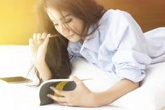 Mujer hermosa que lee un diario en el dormitorio Fotos de archivo libres de regalías