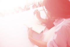 Mujer hermosa que lee un diario en el dormitorio Foto de archivo
