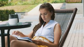 Mujer hermosa que lee un libro al aire libre almacen de metraje de vídeo