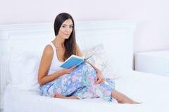 Mujer hermosa que lee un libro en cama Imagen de archivo libre de regalías