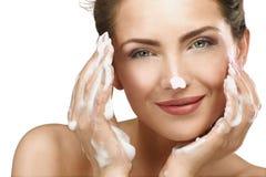 Mujer hermosa que limpia su cara con un tratamiento de la espuma Imágenes de archivo libres de regalías