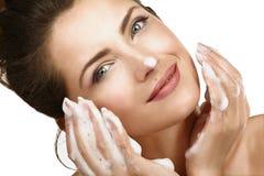 Mujer hermosa que limpia su cara con un tratamiento de la espuma Foto de archivo