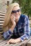 Mujer hermosa que llama por el teléfono en banco en parque Foto de archivo libre de regalías