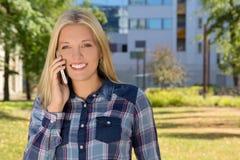 Mujer hermosa que llama por el teléfono en parque del otoño Foto de archivo libre de regalías