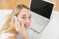 Mujer hermosa que llama por teléfono mientras que miente en su cama al lado de su cuaderno Imágenes de archivo libres de regalías