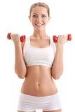 Mujer hermosa que lleva a cabo dos pesas de gimnasia Fotos de archivo libres de regalías