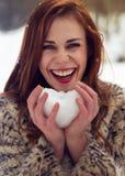 Mujer hermosa que lleva a cabo el corazón de la nieve Foto de archivo libre de regalías