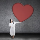 Mujer hermosa que lleva a cabo la muestra en blanco del corazón fotos de archivo