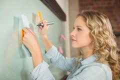 Mujer hermosa que lleva a cabo la nota pegajosa mientras que escribe en el tablero de cristal Foto de archivo
