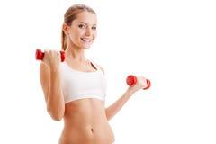 Mujer hermosa que lleva a cabo pesas de gimnasia Imagen de archivo
