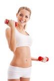 Mujer hermosa que lleva a cabo pesas de gimnasia Imagenes de archivo