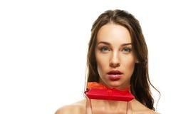 Mujer hermosa que lleva a cabo rojo presente con su finge Imagen de archivo libre de regalías