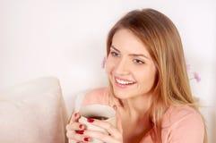 Mujer hermosa que lleva el café de consumición del suéter rosado foto de archivo