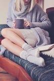 Mujer hermosa que lleva el suéter acogedor y los calcetines calientes de las lanas que leen un libro que se sienta en el sofá cóm Fotos de archivo libres de regalías