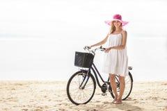 Mujer hermosa que lleva el sunhat rosado que camina con la bicicleta a lo largo de b imágenes de archivo libres de regalías