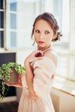 Mujer hermosa que lleva el vestido largo que sostiene la planta de la casa fotos de archivo libres de regalías
