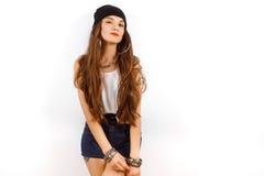 Mujer hermosa que lleva en sombrero negro y la camiseta blanca que se colocan cerca de la pared blanca Fotografía de archivo