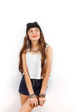 Mujer hermosa que lleva en sombrero negro y música que escucha de la camiseta blanca cerca de la pared blanca, sosteniendo un tel Foto de archivo libre de regalías
