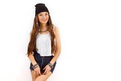 Mujer hermosa que lleva en sombrero negro y música que escucha de la camiseta blanca cerca de la pared blanca, sosteniendo un tel Imagenes de archivo