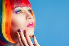 Mujer hermosa que lleva la peluca colorida y que muestra clavos coloridos Imagen de archivo libre de regalías