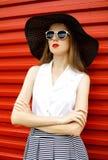 Mujer hermosa que lleva un sombrero de paja negro, gafas de sol y una falda rayada sobre rojo Foto de archivo
