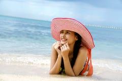 Mujer hermosa que lleva un sombrero que miente en la playa Foto de archivo