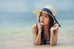 Mujer hermosa que lleva un sombrero que miente en la playa Imagenes de archivo